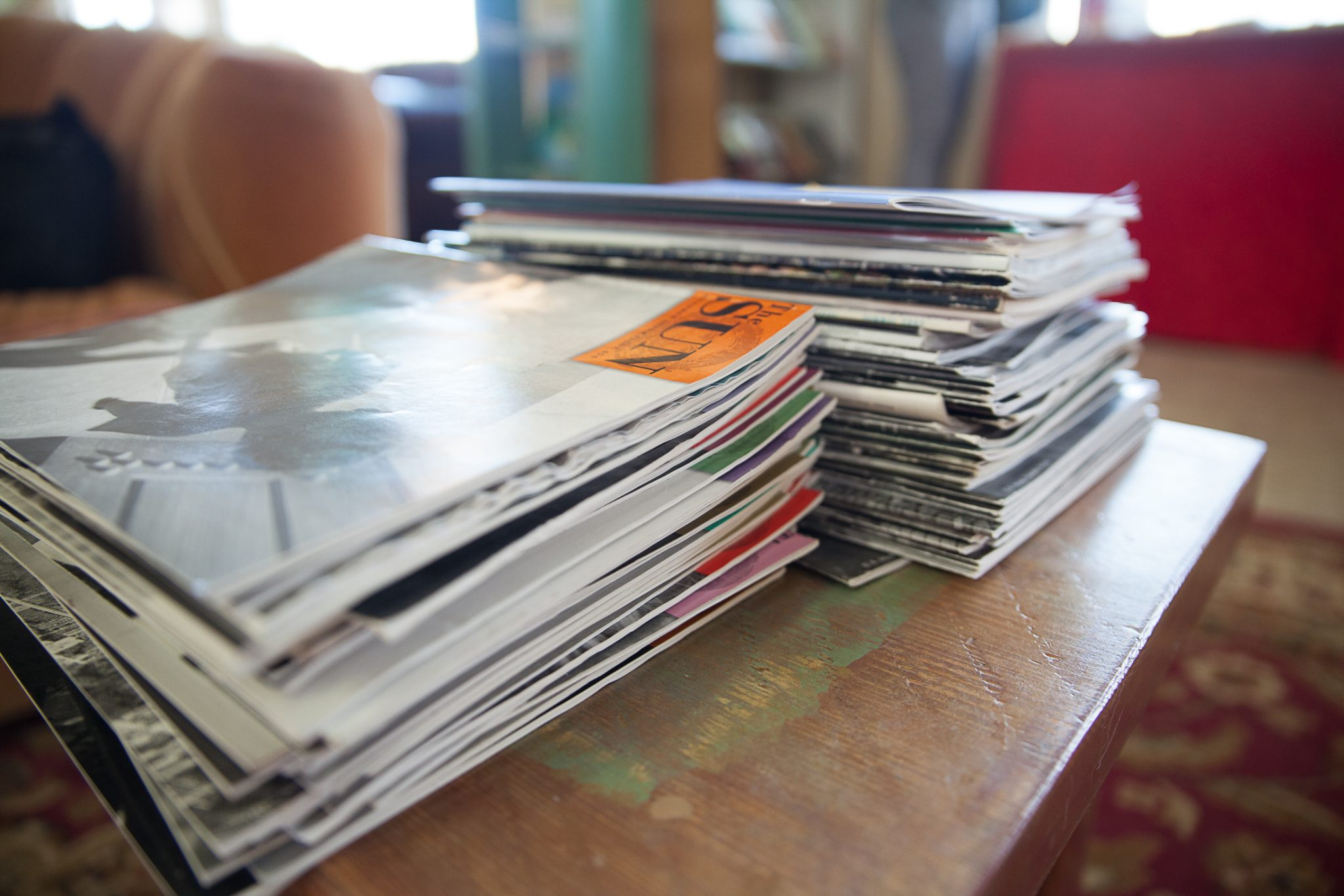 A stack of magazines atop a wooden table at SOMOS in Taos, New Mexico.