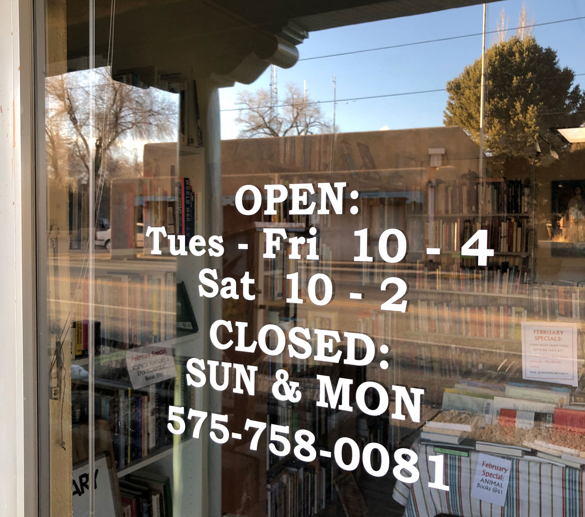 SOMOS front window with store hours