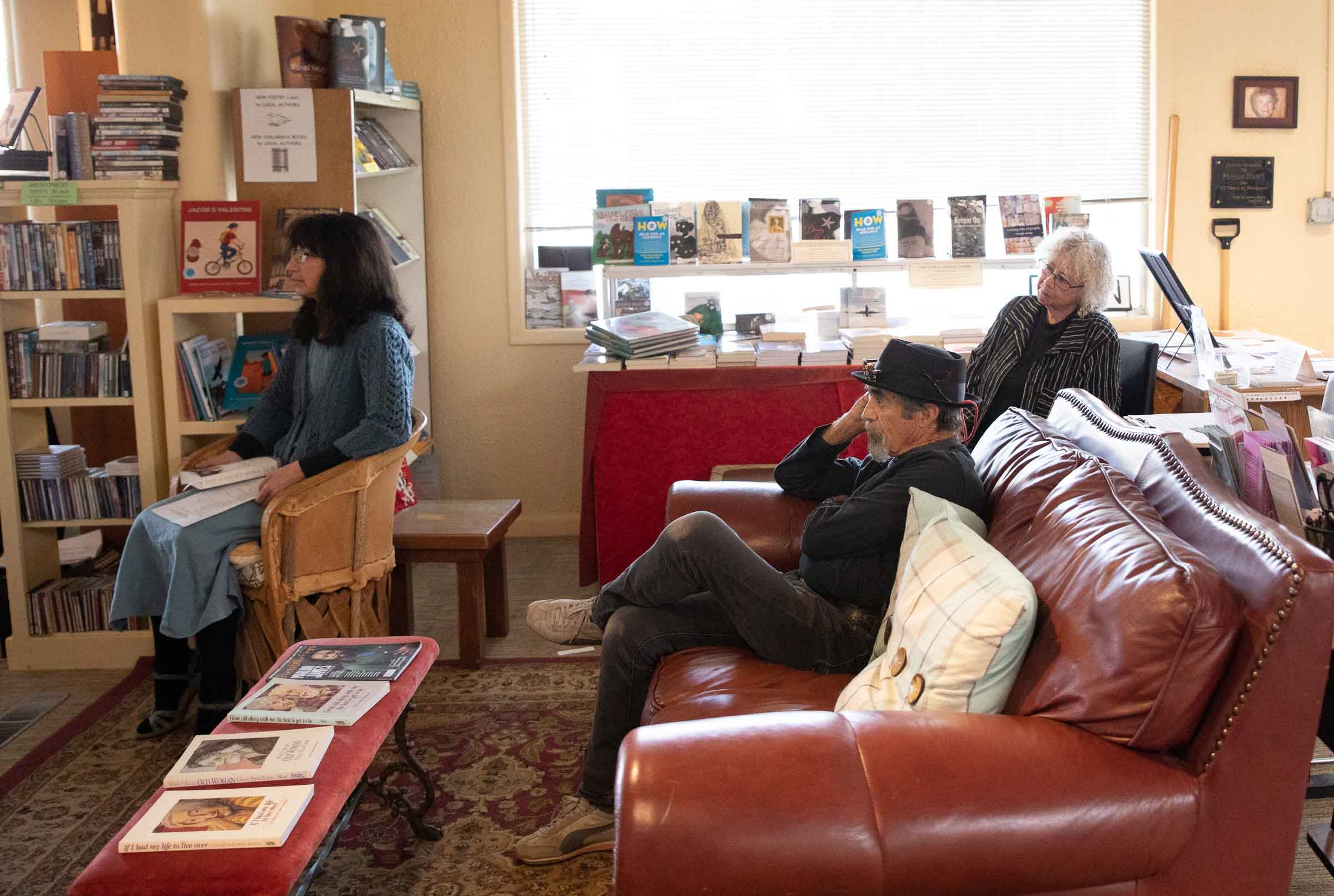 Three people listening to a speaker at SOMOS Boostore in Taos, New Mexico